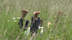 Couple of lower  lie down on green grass barefoot, playing with soles  - stock footage