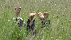 Parents lie down on spring grass,happy child playing on their back  Stock Footage