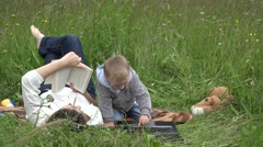 Mother and son in spring field, woman reading book, little child at computer  Stock Footage