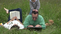 Stock Video Footage of Father working in the park, child disturb man job, mother reading book