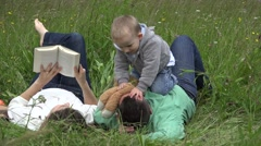 Mother reading a book, little son play with father, child torture man outdoor  - stock footage