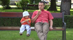 Father and son sitting on the bench in the park eating corn on the cob, apple  - stock footage