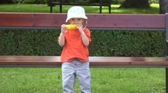 Lovely child eating corn on cob outdoor. Summer park  - stock footage