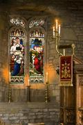 Church pulpit and stained glass window with lit candles Stock Photos
