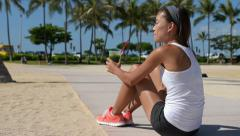 Healthy woman runner drinking green smoothie relaxing after running Stock Footage