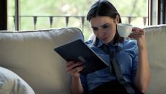 businesswoman reading news on tablet computer while sitting on sofa  HD - stock footage