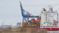 Container ship motion along port buildings and cranes 4k Stock Footage
