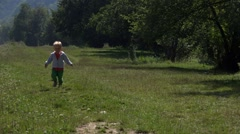 Lovely blond boy running to green meadow  Stock Footage
