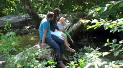 Young parents and little child sitting on tree trunk above mountain river 4k Stock Footage