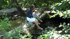Young mother and little son resting on tree trunk above mountain river 4K - stock footage