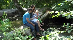 Young family rest on tree trunk and throwing off the stones in mountain river 4k - stock footage