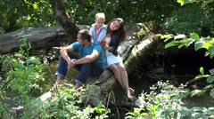 Lovely child and parents rest, tree trunk over mountain river Feel the summer 4k - stock footage