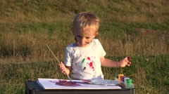 Stock Video Footage of Amusing baby boy painting in the park