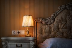 lamp on a night table next to a bed - stock photo