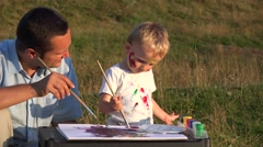 Father and son spending time together in nature. Man and child painting  - stock footage
