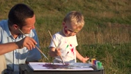 Stock Video Footage of Father and son spending time together in nature. Man and child painting
