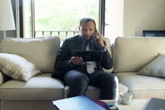 Businessman with tablet computer talking on cellphone sitting at sofa  NTSC - stock footage