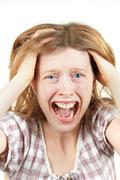 young woman screaming in agony with mouth wide open holding head - stock photo