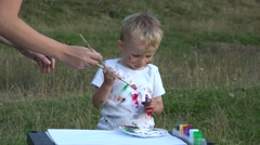 Mother hand and little child painting together in nature. Happy moments  - stock footage