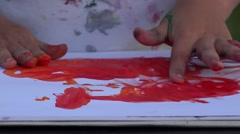 Close up the baby child hands painting with red color  Stock Footage