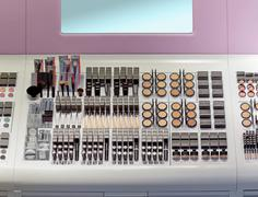 makeup counter inside beauty store with shelf full of makeup products - stock photo
