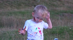 Amusing little boy painting his face in nature 4k - stock footage