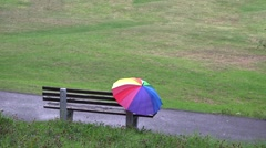Rainbow colored umbrella abandoned on empty bench in the park, loneliness  Stock Footage