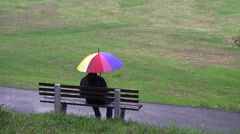 Little child coming to father sitting on the bench in park, rainy whether  - stock footage