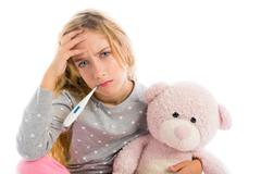 blond girl with thermometer and flu cold in pyjama - stock photo