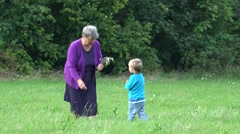 Grandmother and grandson gathering flowers together close green forest  Stock Footage