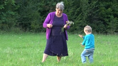 Little grandchild and his grandmother in spring nature, happy toddler jumping  Stock Footage
