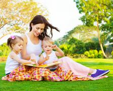 Woman with daughter and son read fairytale Stock Photos