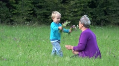 Happy blond grandchild arrange flower coronet on grandmother head  in nature 4k - stock footage