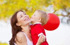 Little boy kissing mom Stock Photos