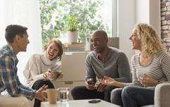 Friends hanging out in living room - stock photo