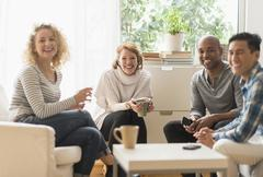 Group of friends hanging out in living room - stock photo