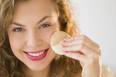 Stock Photo of Young woman applying make up foundation