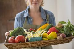 Stock Photo of Young woman holding tray with vegetables