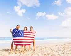 Young people holding American flag on beach - stock photo