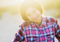 Stock Photo of Portrait of young woman in sunlight, smiling
