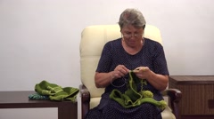 Active grandmother with eyeglasses crocheting a green scarf 4k Stock Footage