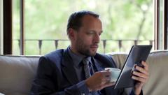 Stock Video Footage of Businessman reading article on tablet computer and drinking coffee on sofa  HD
