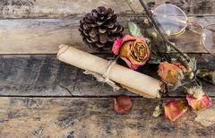 old paper roll, glasses,and dry rose on wooden - stock photo