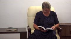 Happy grandmother reading a book and smiling 4k - stock footage