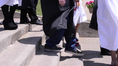 Graduation cap and gown walking foot shot Stock Footage