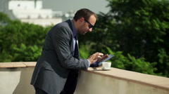 Young businessman working on tablet computer standing on the terrace  HD Stock Footage