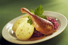 roast duck, red cabbage, dumplings and gravy. - stock photo