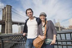 Stock Photo of Couple leaning against railing and looking at camera