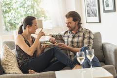 Stock Photo of Cheerful couple eating on sofa