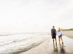 Stock Photo of Young couple walking along surf line of sandy beach, holding hands